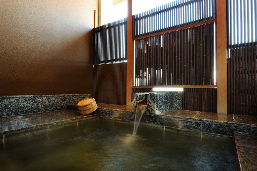Indoor hot spring bath at Kai Matsumoto with bath bucket on left.